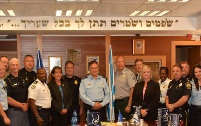 "A 2014 delegation of American law enforcement officials organized by GILEE visits the Israeli police commissioner's office. The Hebrew inscription on the wall is from Deuteronomy 16:18: ""You shall appoint judges and officers in all your gates."""