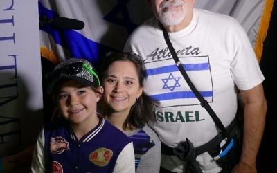 Stanley Greenstein and Stacy and Alia Lord pose with the Israeli flag after recording a video birthday wish for Israel in the AJT Chill Zone.