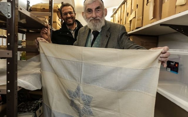 "Ezra Gorodesky holds the flag Rebecca Affachiner, known as the ""Betsy Ross of Israel,"" made and first flew after David Ben-Gurion proclaimed the state of Israel on May 14, 1948. (Photo by Dani Machlis, Ben-Gurion University)"