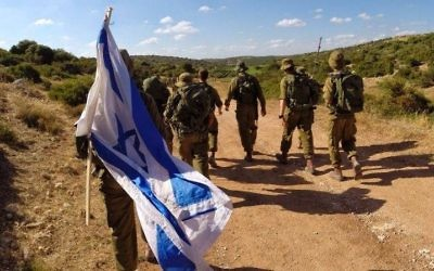 IDF soldiers march with the Israeli flag.