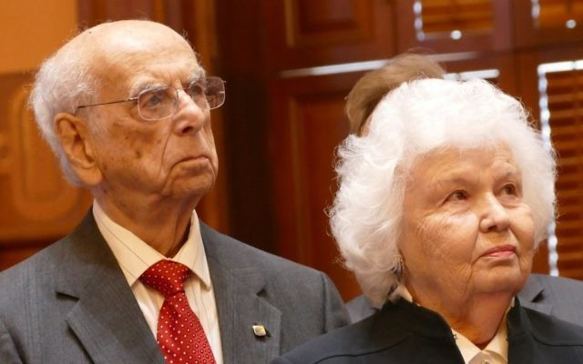 Fred and Tosia Schneider listen to their life stories after placing the first of the six candles at the ceremony.