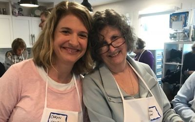 Caryn Hanrahan (left) and Jeanney Kutner prepare treats for Holocaust survivors.
