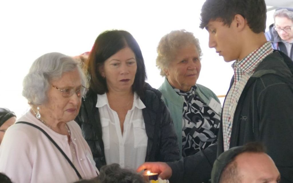 The past and future of remembrance come together as a student helps a Holocaust survivor light a candle during the Yom HaShoah ceremony at the Memorial to the Six Million on April 15.
