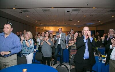 Rabbis Daniel Dorsch and Shalom Lewis (right) lead a standing ovation for Jerry Quan.