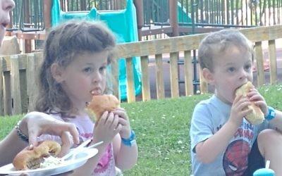 Attendees enjoy hot dogs and hamburgers at Chabad of Cobb's Lag B'Omer picnic.