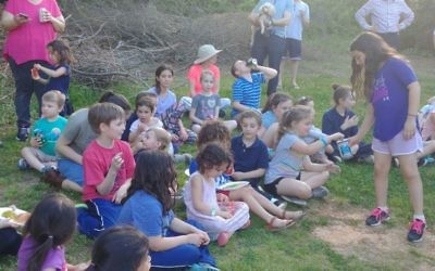 A young girl collects tzedakah at the picnic, following through on the rabbi's lesson.