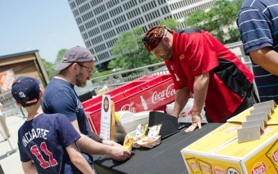 Keith Marks of Keith's Corner BBQ serves Kosher Day customer Brett Cohen at the Braves game May 6. (Photo by Eli Gray)