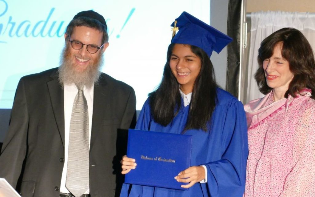Head of School Rabbi Michoel Druin and school founder Dassie New present the first diploma in the history of the Chaya Mushka Children's House Elementary & Middle School to Miriam Farkas.