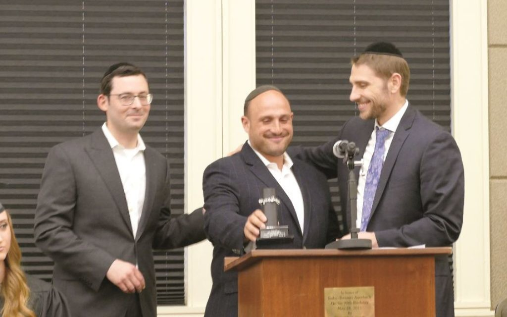 Executive Director Rabbi Yitzchok Tendler presents a tribute to Shalom Teller  for his service with presenter Rabbi Doron Silverman (right)