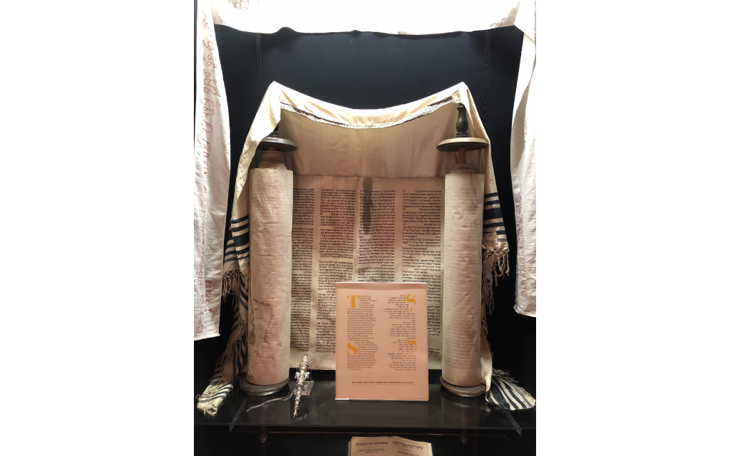 The Holocaust-era Torah from the Czech Republic is on display at AAs Sylvia G. Cohen Museum draped in a frayed tallit.