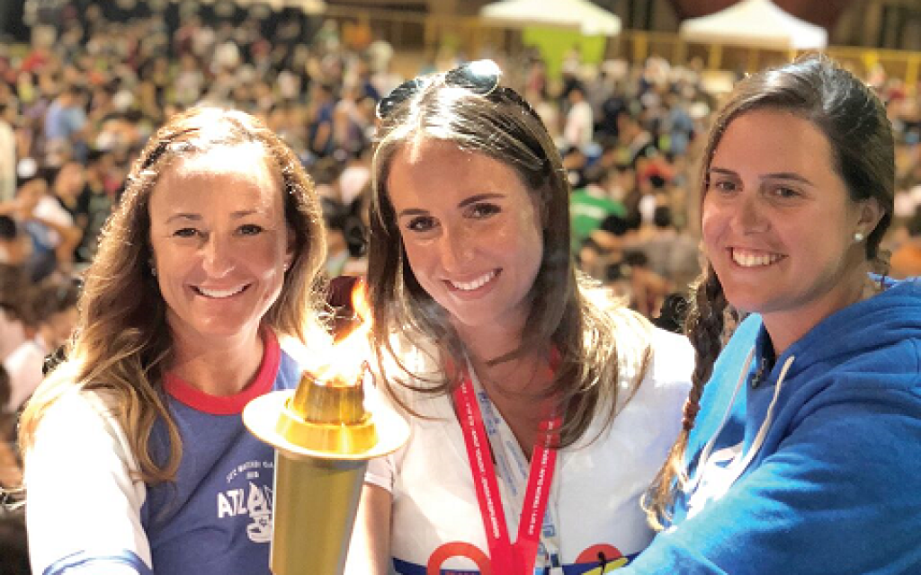 Passing  the  JCC  Maccabi  Games  torch  during  the  closing  ceremonies  in  Orange  County,  Calif.,  on  August  9,  2018  are  (L-R):  Stacie  Francombe,  2019  Atlanta  Games  Director;  Sam  Cohen,  2018  Orange  County  Games  Director;  Carissa  Mindt,  2019  Atlanta  Games  Assistant  Director.