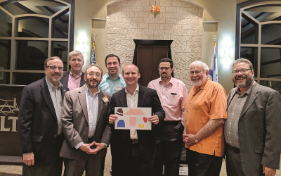 Showing off artwork are Rabbis Neil Sandler (AA), Laurence Rosenthal (AA), Mark Zimmerman (Beth Shalom), Hillel Konigsburg (B'nai Torah), Dan Dorsch (Etz Chaim), Josh Heller (B'nai Torah), Shalom Lewis (Etz Chaim) and Michael Bernstein (Gesher L'Torah).