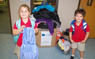 Hazel Halitsky and Rafi Breslav-Siller show how Davis lower school families donated coats to Simple Needs GA during the Su-Coat winter clothing drive.