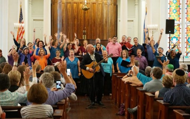Choir Director Will Robertson plays his guitar along with the choir as they perform at the Piccolo Spoleto Festival in Charleston, S.C.