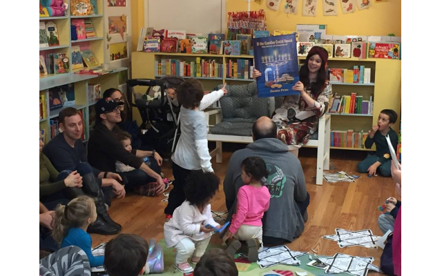 Bracha Slavaticki of Chai Decatur reads Chanukah books to children at Little Shop of Stories.