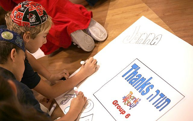 Second-grader Jordan Smith, top, and fourth-grader Jude Beale, sign a poster about giving thanks at Epstein's Tikkun Olam Service Learning Day.