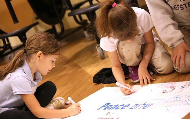 Sofia Harber, an Epstein first-grader, and fourth-grader Wren Woodman, write their names and messages of peace on a poster for Tikkun Olam Service Learning Day.