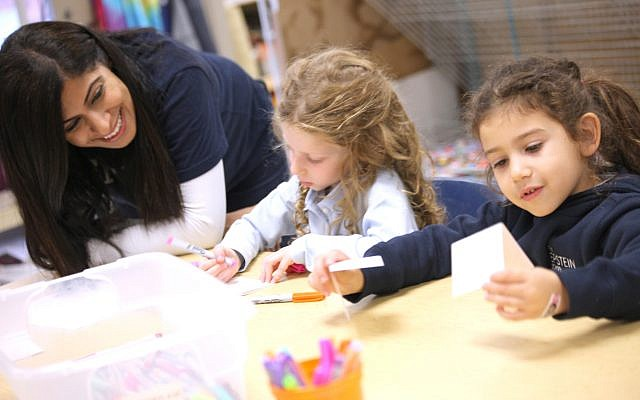 Teacher Poonam Bakshani talks to kindergartners Abigail Kauss and Amelia Antebi about the messages of thanks, love, charity, community, friendship, joy and good deeds.