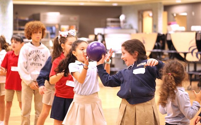 Third-grader Kayla Milrad passes a ball backwards to teammate, second-grader Alexis Shulman, as part of a teambuilding activity.
