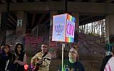 "Congregation Bet Haverim Rabbi Joshua Lesser held aloft a lighted CBH sign as congregant Brad Davidorf, on guitar, led congregants in Chanukah songs, including the Ladino ""Ocho Kandelikas."""