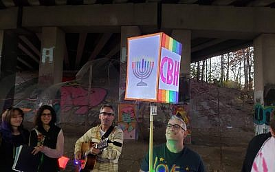 "Congregation Bet Haverim Rabbi Joshua Lesser held aloft a lighted CBH sign as congregant Brad Davidorf, on guitar, led congregants in Chanukah songs, including the Ladino ""Ocho Kandelikas."""