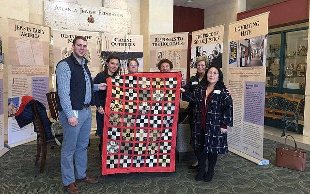 Jeremy Katz of the William Breman Jewish Heritage Museum and Renee Kutner of the Jewish Federation of Greater Atlanta receive a quilt from members of the Oak Grove United Methodist Church.