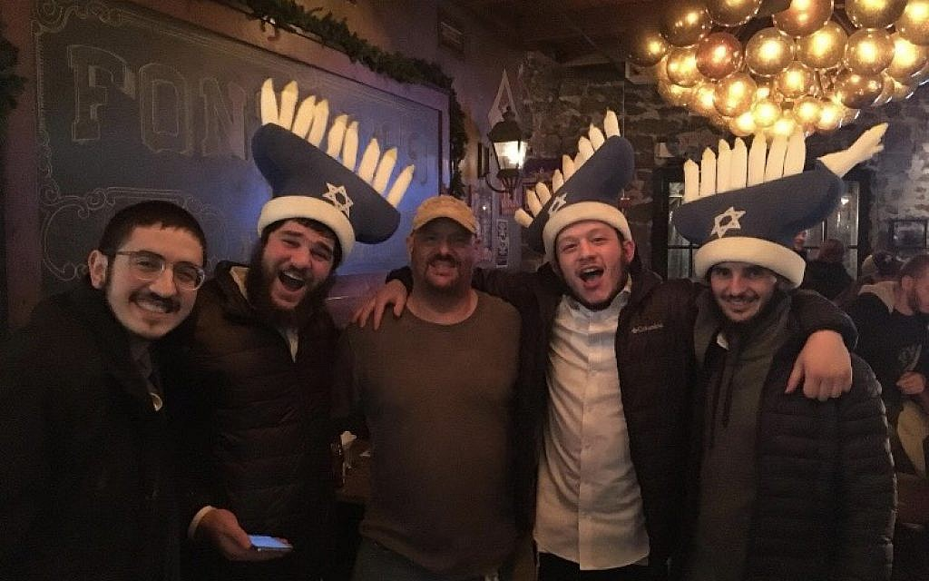 Out on the town rabbis enjoy the holiday spirit, complete with funny menorah hats.