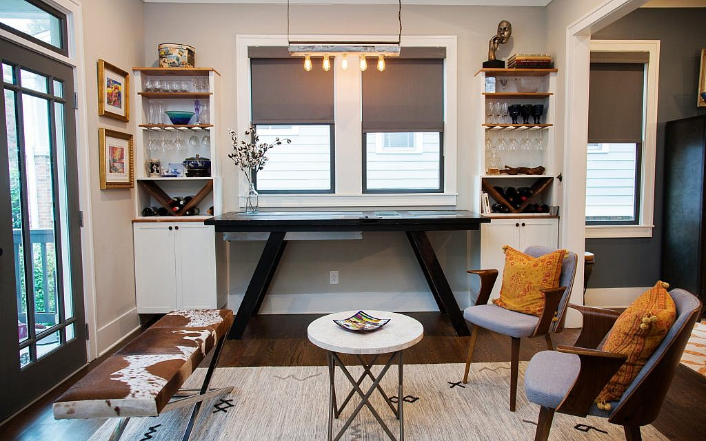 A faux cow print bench sits alongside a bar constructed from an old door with an ice storage cabinet. Lauren saw the idea of a bar with an inlaid ice bin, and worked with a reclaimed furniture carpenter to design it using an antique door, custom-formed galvanized steel trays and glass panels.