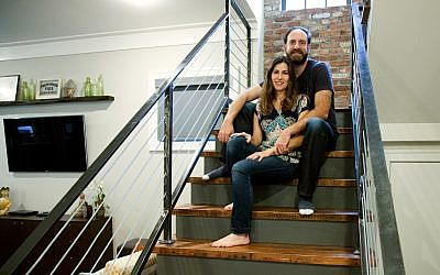 Photos by Laurie Sermos // Lauren and Mark Chekanow relax on the repurposed wood stairs in front of the brick wall that was restored from the original fireplace.