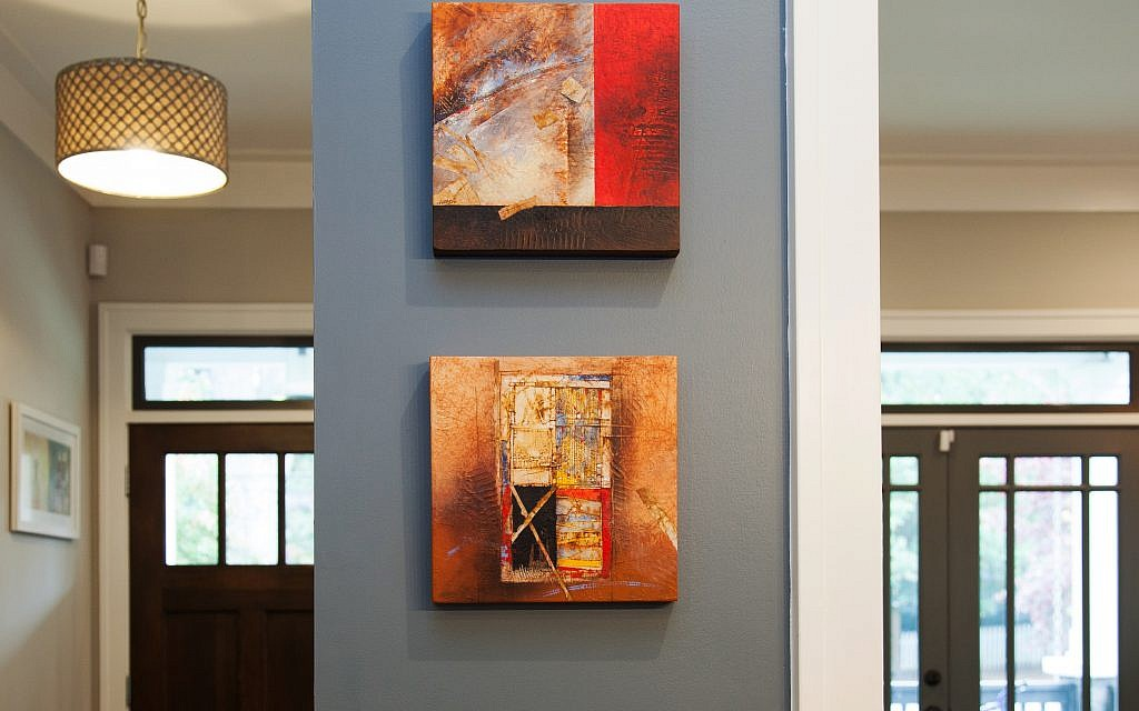 Crimson paintings by Bordeau Macio share a front entry wall.