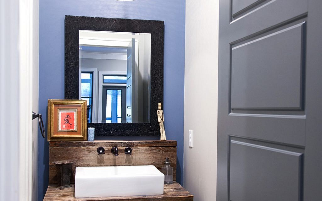 The guest bath counter is made from recycled wood. The light fixture was the first item the couple bought for the project.