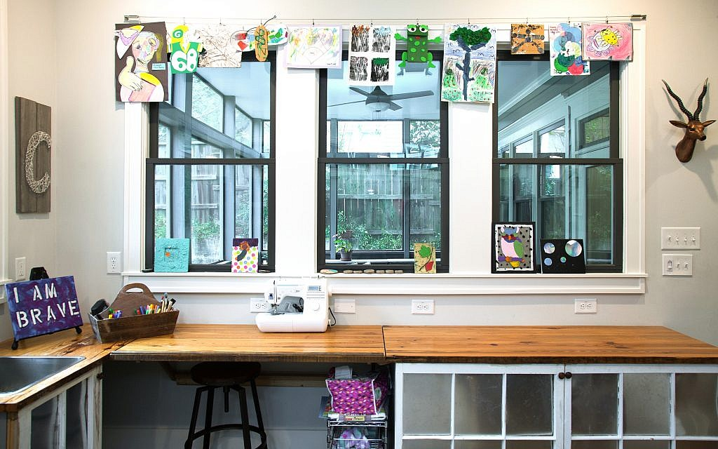 The art room overlooks the outdoors and has ample storage for toys in cubbies made from reclaimed wood, old windows and tin panels.