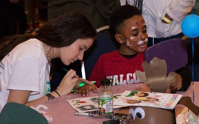 A teen volunteer paints a child's face and hands.