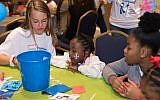 Photos by Eddie Samuels // Children enjoy games and activities led by volunteers in the carnival room.