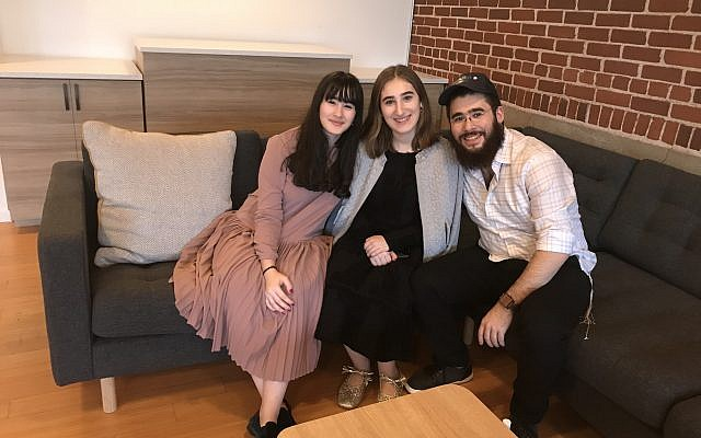 Mira, 14, Sara, 17, and Mutik, 22, three of the Schusterman children, on one of the café's sofas, helped make the day a success. Mutik emceed and Sara and Mira took care of last-minute preparations.