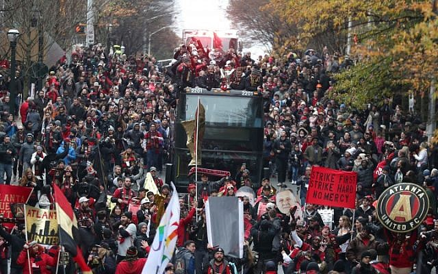 Atlanta United players ride on a bus amidst crowds of fans.
