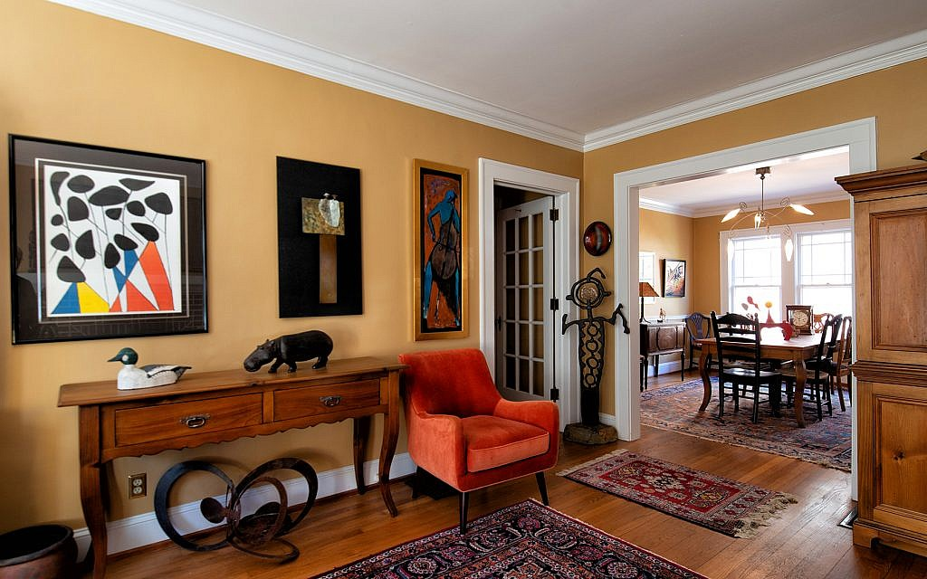 """Dr. Padwa's Room features a Calder limited lithograph, San Francisco; """"Lovers Sharing Poncho,"""" bronze relief by Guilloume; """"Cello"""" by Collin Varsan, New York City;  wooden hippo from Nairobi and a collected duck decoy. Far right: Metal sculpture of a human form by artist Terri Stone."""