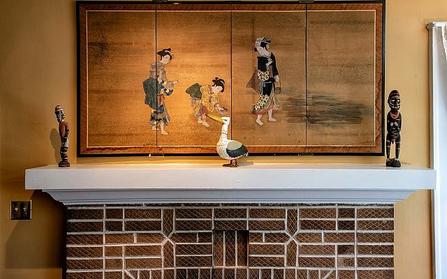 Above the mantel is a Asian Japanese silk screen (1840), which Padwa bought in 1973 in Japan. Adjacent to the silk screen are small Australian sculptures. The wooden decoy is part of his 1960s collection.