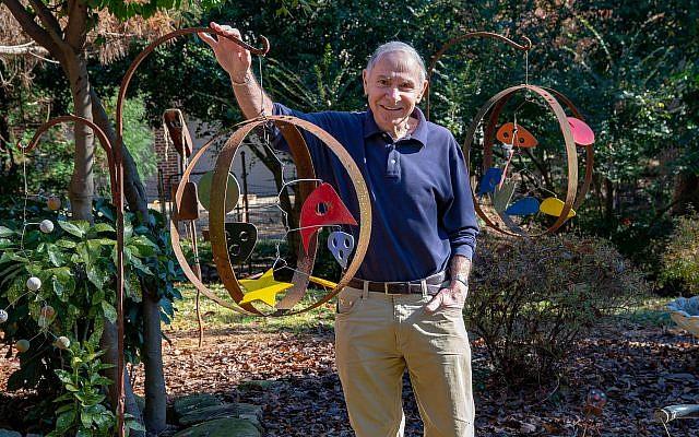 Photos by Duane Stork // Dr. Al Padwa cradles one of his metal globes in his backyard sculpture garden.