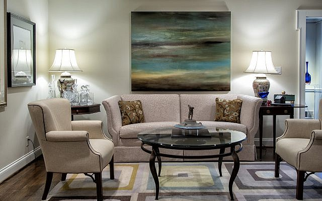 """Behind the couch is one of Wilensky's earlier (2008) acrylic blends reflecting the mountains upon the sea, entitled """"Sunset,"""" which took two weeks to complete.  The rug was custom-designed and woven for Wilensky by a fellow artist."""