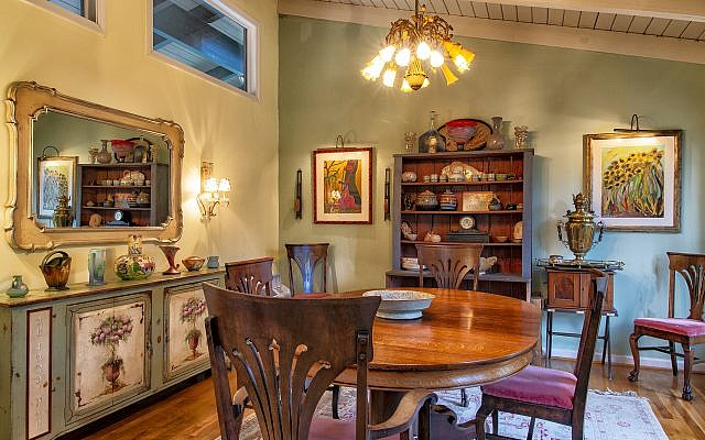 "The country French décor highlights art, from left, Costa Rican Patricia Erickson, cabinet of treasured china and pottery, Russian samovar from great-grandmother, and ""Sunflowers"" by Woodie Long, folk artist from the Florida Panhandle."
