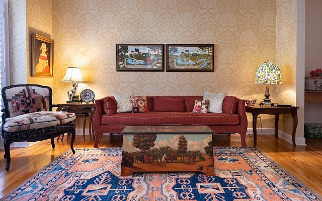 """Living Room: Holtz designed the upholstered chair on left from antique quilts. The original oil on the left is titled """"Girl With Antique Doll."""" Sheila bought the hand-painted chest in the center from Scott Antique Market. The original watercolor pair behind the couch is from Joseph Valley Family Farm (1910). The salmon and royal blue rug is an antique Kilim."""