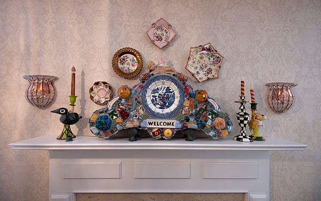 Steve Terlizzese specializes in maximalist conglomeration of tile, glass, and pottery. The master bedroom fireplace shows his Blue Willow mantel clock. The dishes around the clock are discontinued antique fine china patterns.
