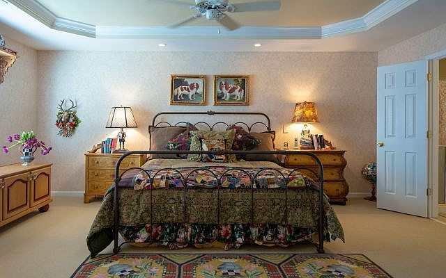 Linens are by Ralph Lauren, two antique unmatched chests serve as end tables next to the antique rusted wrought iron bed. The floor covering is Mackenzie-Childs. Antique King Charles Spaniel oils by Lee Kennedy are above the master bed.