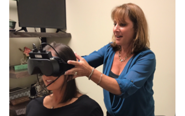 Dr. Peggy Marbach tests a patient using infrared video goggles.