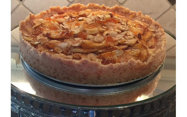 This round cake is the apple cream cheese torte. Buttery sweet crust with cream cheese filling, topped with sliced fresh apples sprinkled with sugar and cinnamon, brushed with apricot glaze.