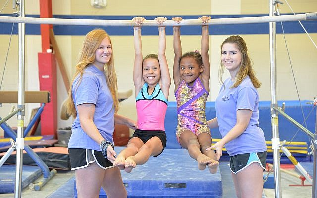 Young athletes practice gymnastics with the aid of instructors.