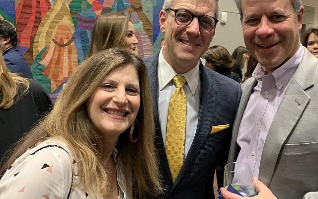 Jill Stouman and Larry Stoumen from Beth Shalom flank Temple Sinai's Rabbi Ron Segal.