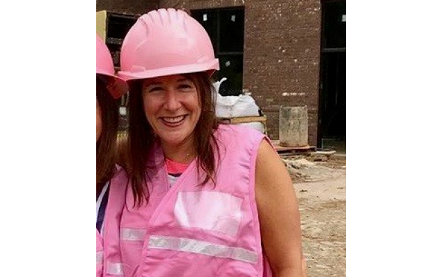 Amy Fingerhut in a pink hardhat on a construction site.