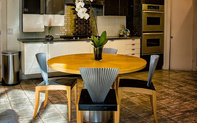 The metal fan backed chairs surround the Italian eat-in kitchen table.